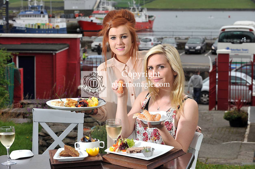 5-10-2012: PR PHOTO: Anyone for Dingle Bay Prawns.... Dingle girls Jessica Hennessy, left and Jane Prendeville tuck into some local fish products including Dingle Bay Prawns and Crab fresh from the sea at The Boatyard Restaurant on the opening day of the Dingle Food Festival and Blas na h-Eireannn awards which are taking place all weekend in the County Kerry seaside town. The festival will feature the national food awards, taste trails, kiddies bus grub, food demonstrations and much more. See www.dinglefood.com..Picture by Don MacMonagle..PR photo from Dingle Food Festival