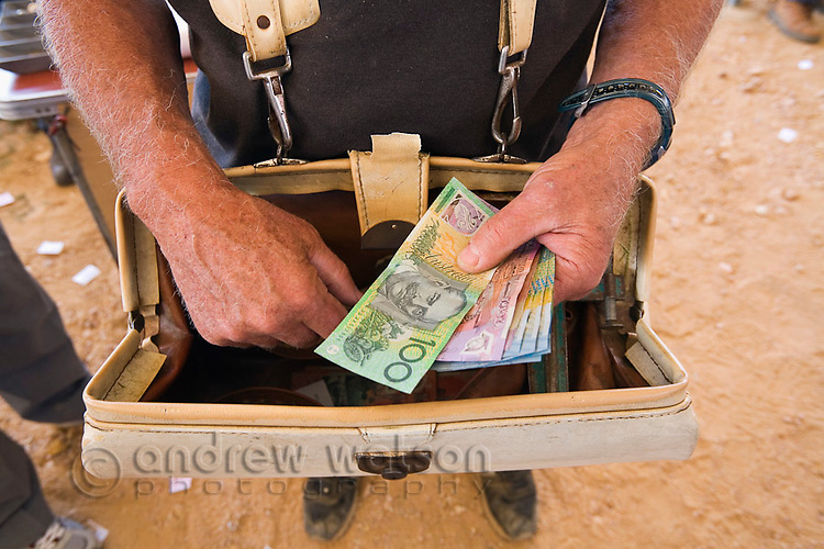 A bookie with his money bag at the Birdsville Cup horse races.  Every September thousands of horse racing enthusiasts arrive in the outback town on the edge of the Simpson Desert for the famous racing carnival.  Birdsville, Queensland, AUSTRALIA.