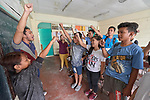 "Larren Jo ""LJ"" Bacilio (left), a teacher in the Alternative Learning System of the Kapatiran-Kaunlaran Foundation (KKFI), raises a fist with his students at the end of a class in the Tondo neighborhood of Manila, Philippines. <br /> <br /> KKFI is supported by United Methodist Women."