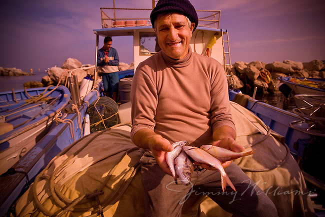 An elderly Italian fisherman shows some of the fish he caught.