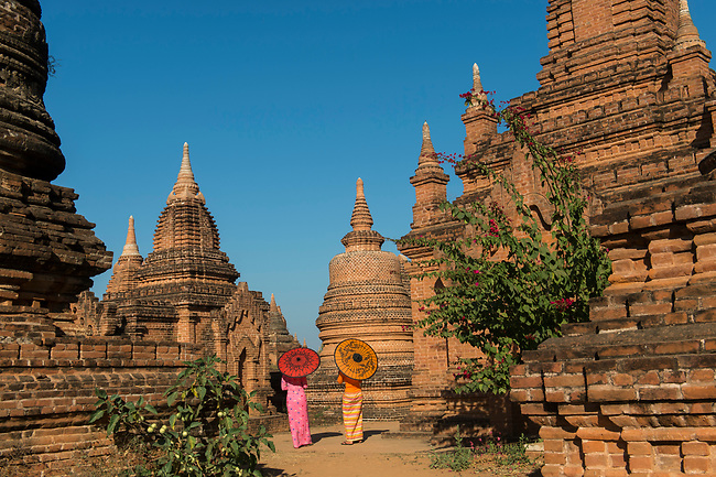 A model shoot with two young women in traditional dress and parasols at a small temple complex in Bagan, Myanmar walking away from the camera.