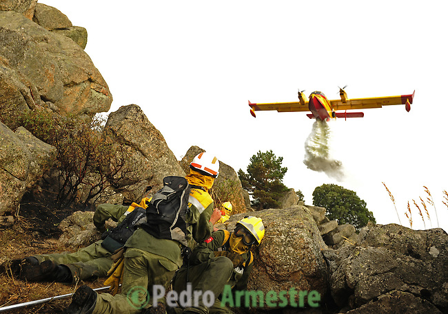 Firefighters take cover as a plane drops water on a fire burning on July 21, 2009, in the Cerro del Castillo hill, near the town of Collado Mediado, northeast of Madrid, which forced the evacuation of some 2,000 people, the mayor of the town, Maria Rubio, told news radio Cadena Ser. Four firefighters were killed and two were seriosuly injured Tuesday as they battled another wildfire in a natural park in northeastern Spain, a spokeswoman for the local government said. on July 21, 2009. (C) Pedro ARMESTRE
