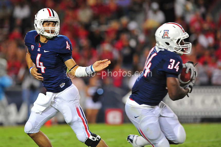 Sept 11, 2010; Tucson, AZ, USA; Arizona Wildcats quarterback Matt Scott (4) hands the ball off to running back Greg Nwoko (34) in the 2nd half of a game against the Citadel Bulldogs at Arizona Stadium.  Arizona won the game 52-6.