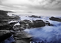 Waves surge over the rocky shores of Acadia National Park, Maine..(hand colored)