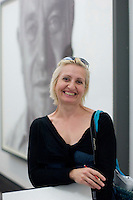 Art teacher sketching with portrait of Sir Paul Nurse by Jason Brooks behind her, State Secondary school visit to the National Portrait Gallery, London.