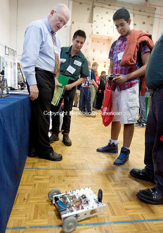 WINSTED CT. 03 May 2013-050313S08-From left, Frank Gregorio of Technical Education Solutions explains about a robotic program to Thomas Whalen, 19, of Bristol Tech. and Victor Rosario o, 15, of Torrington High during the manufacturing career expo at Northwestern Conn. Community College in Winsted Friday. About 250 students from 10 Northwest Connecticut high schools, and about 20 manufacturing companies attended the event sponsored by CBIA Education Foundation..Steven Valenti Republican-American