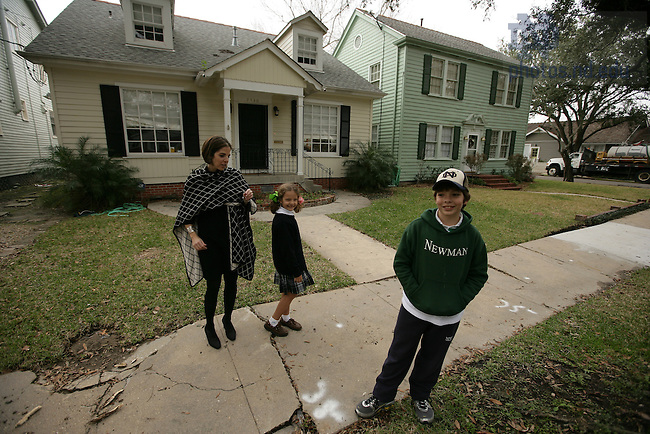 Helen Smith, '92 and her daughter Julia, 7 and son George, 11 stand outside of their home which was flooded in the aftermath of the storm.  They stayed with relatives for six months while their home was repaired.