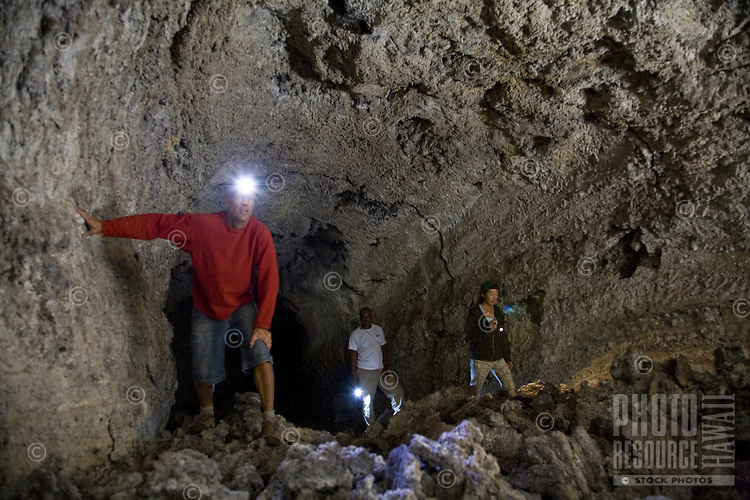 A group of hikers exploring a lava tube cave in the Haleakala Crater