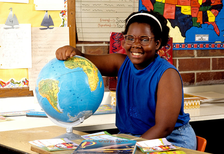 Black African American girl age 12 in seventh grade learning from globe about the worl