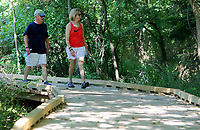 NWA Democrat-Gazette/DAVID GOTTSCHALK  Linda McMath (right), Botanical Garden of the Ozarks board president, walks with her husband Bob Monday, July 10, 2017, on a new section of trail at Lake Fayetteville near the gardens in Fayetteville. An new 800 feet section of of board walk and bridges recently opened rerouting a small portion of the soft trail. Rough cut cedar planks were used as the decking.