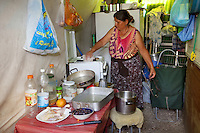 Italy. Lazio region. Rome. Tor di Quinto area. Gypsy camp. A gypsy woman, romanian citizen, is standing in the kitchen oustide her wooden shack. She cleans her stove after having cooked some food. She lives permanently as an immigrant in Italy. The Romani, who are known collectively in the Romani language as Romane or Rromane (depending on the dialect concerned) and also as Romany, Romanies, Romanis, Roma, Romsor or Rroms, are an ethnic group living mostly in Europe. Romanian immigration. 29.09.2011 © 2011 Didier Ruef