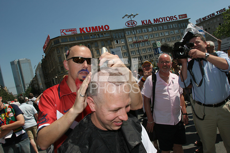 USA fan Zack Phillips, of San Francisco, Calif. shaves the hair of Canadian soccer fan Yuri Smieska of Hamilton, Ontario  into the design of a soccer ball outside the Frankfurt Main Train Station in Frankfurt-am-Main, Germany on Tuesday, June 13, 2006.
