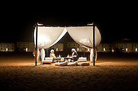 Two people sit chatting in a tented sitting area in the centre of the desert camp