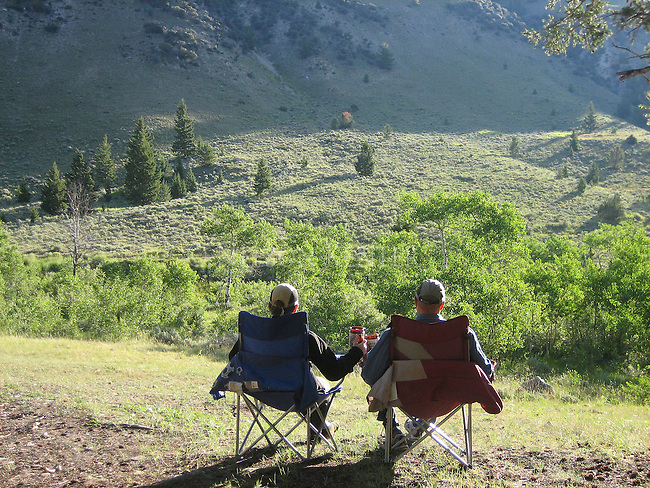 A Couple enjoys the sunrise in a campground in southwest Montana near the Lima Peaks