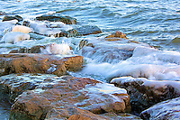 Waves splash over icy rocks in early winter in Lake Ontario