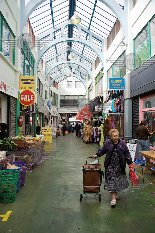 A woman wheels her shopping trolly through Brixton's indoor market in South London.
