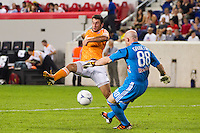 Will Bruin (12) of the Houston Dynamo attempts to block the clearance of New York Red Bulls goalkeeper Bill Gaudette (88). The New York Red Bulls defeated the Houston Dynamo 2-0 during a Major League Soccer (MLS) match at Red Bull Arena in Harrison, NJ, on August 10, 2012.