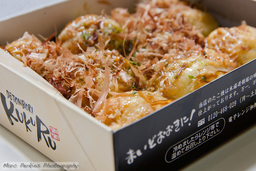 A box of eight completed Takoyaki, made during a demonstration of takoyaki cooking at Mitsuwa Market in Costa Mesa, California.  The takoyaki are topped with a mayonnaise sauce, a second darker sauce, and then sprinkled with shaved bonito (dried fish).