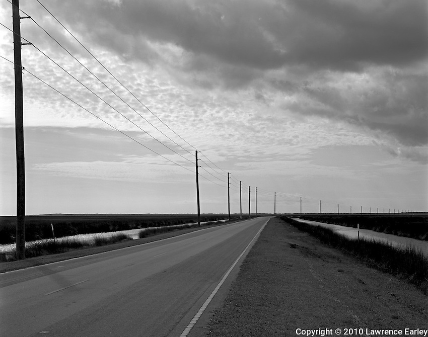 Telephone poles show the distance along Rt. 12 crossing the vast salt marshes of Cedar Island National Wildlife Refuge in North Carolina.