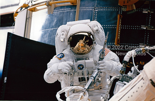 Astronaut Steven L. Smith picks-up a power ratchet tool as he prepares to join astronaut Mark C. Lee (out of frame) on the first spacewalk of the STS-82 mission to service the Hubble Space Telescope (HST), temporarily latched down on Discovery's cargo bay (background).<br /> Credit: NASA via CNP