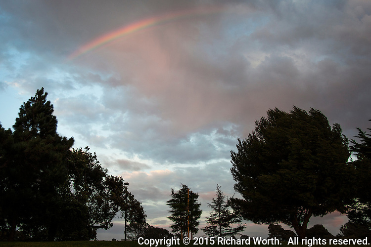 A rainbow appears over a city park as clouds glowed sunset orange.