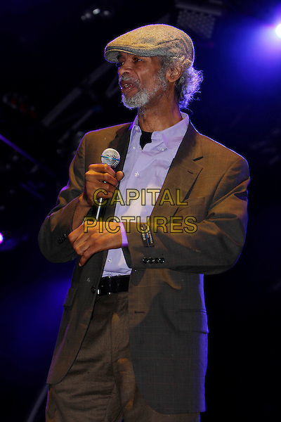 GIL SCOTT HERON.Performing live in concert at Somerset House, London, England, UK, .14th July 2010..music concert gig on stage half length cap hat microphone beard facial hair brown grey gray suit .CAP/MAR.© Martin Harris/Capital Pictures.