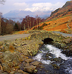 Winter view of Ashness Packhorse Bridge looking over Derwent Water to Skiddaw