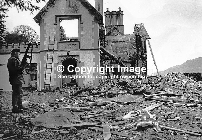 A soldier on duty at the burnt-out remains of the home of Major Ivan Neill at Rostrevor, Co Down, N Ireland, UK. The December 1971 fire was a result of an arson attack by the Official IRA who had a few months earlier failed to kidnap Major Neill from his home. Major Neill is the Speaker of the N Ireland Parliament at Stormont. 197112300554c. <br />