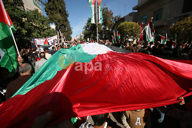 People march with giant Palestinian flags during a rally supporting the Palestinian UN bid for observer state status, in the West Bank city of Hebron, Thursday Nov. 29, 2012. The Palestinians are certain to win U.N. recognition as a state on Thursday but success could exact a high price: delaying an independent state of Palestine because of Israel's vehement opposition. Photo by Mamoun Wazwaz