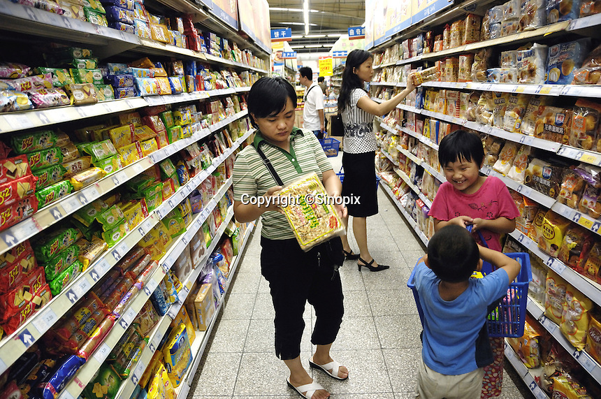 A lady checks a pack of cake in Wumart supermarket in Beijing, China. China's inflation rate last month soared to its highest level in more than a decade, sounding new alarm bells that will likely lead to further monetary tightening..13 Aug 2007