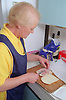 Elderly carer preparing sandwich for client,