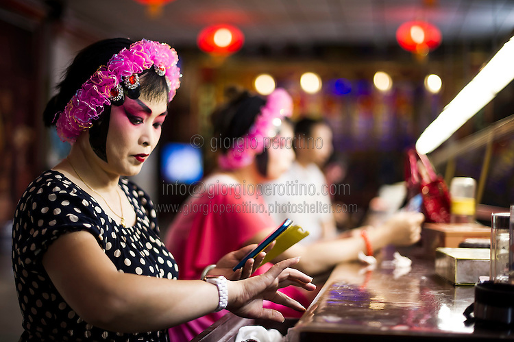 A Chengdu Opera actress checks her clock and smartphone as she prepares for the show in the backstage of the Opera Tea House in Chengdu, Sichuan, August 12, 2014.<br /> <br /> Smartphones are an essential tool of Chinese ordinary life. Everywhere in China, people use them to take pictures to share online, to talk and chat, to play videogames, to get access to the mainstream information, to get connected one each other. In the country where the main global social media are forbidden - Facebook, Twitter and Youtube are not available  -, local social networks such as WeChat have a wide spread all over the citizens. The effect is an ordinary and apparently compulsive way to get easy access to digital technology and modern way of communication. <br /> A life through the display. Yes, We Chat.<br /> <br /> © Giorgio Perottino