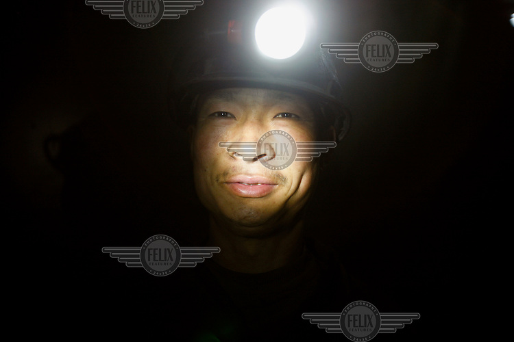 A coal miner is illuminated by his headlamp inside the shaft of a state-owned mine.