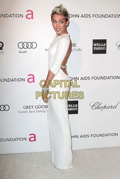 Miley Cyrus (wearing Azzaro).The 21st Annual Elton John AIDS Foundation Academy Awards Viewing Party held at The City of West Hollywood Park in West Hollywood, California, USA..February 24th, 2013.oscars full length dress white long sleeves diamond bracelets chains straps backless  side  .CAP/ADM/KB.©Kevan Brooks/AdMedia/Capital Pictures.