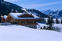 The chalet surrounded by snow with a view of the mountains beyond