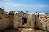 Low angle view of a stone window frame in the Mnajdra Temple complex, c.3600-3200 BC, Malta, pictured on June 5, 2008, in the morning. The Republic of Malta consists of seven islands in the Mediterranean Sea of which Malta, Gozo and Comino have been inhabited since c.5,200 BC. It has been ruled by Phoenicians (Malat is Punic for safe haven), Greeks, Romans, Fatimids, Sicilians, Knights of St John, French and the British, from whom it became independent in 1964. Nine of Malta's important historical monuments are UNESCO World Heritage Sites, including  the well preserved Mnajdra Temple complex. Spectacularly sited on the Southern coast of Malta the three temples radiate from an oval forecourt. The lower temple is astronomically aligned so that the sun's rays shine straight through the doorway on the equinoxes. Picture by Manuel Cohen.