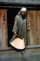 A KASHMIRI WOMAN holding a woven DUSTPAN in her HOUSE BOAT on the JHELUM RIVER - KASHMIR, INDIA.