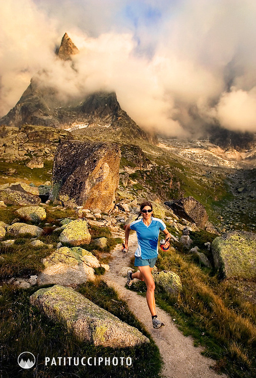 A female trail runner running beneath the dramatic spires of the Aiguilles du Midi high above Chamonix Valley