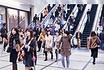 People on train station escalators in Osaka, Japan
