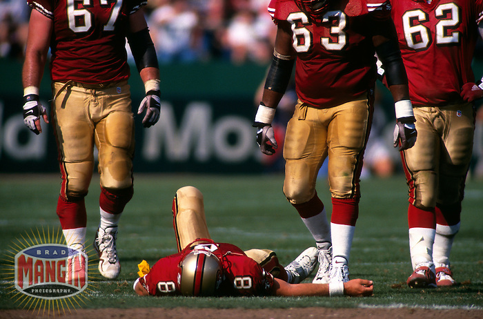 SAN FRANCISCO, CA -  Quarterback Steve Young of the San Francisco 49ers lies down on the ground hurt during a game against the New Orleans Saints at Candlestick Park in San Francisco, California in 1999.  Photo by Brad Mangin