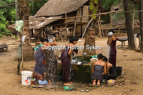 Young women washing at the village water trough. Myn-Ka-Ba village, Bagan, Myanmar South East Asia 2006 ( Burma )
