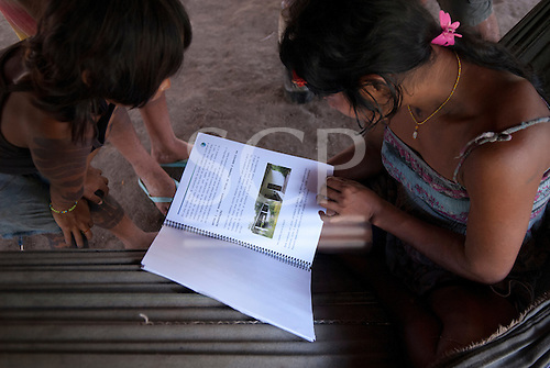 Aldeia Baú, Para State, Brazil. A Kayapo mother reading from a book while her daughter looks on.