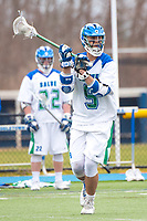 Eric Backus,'17, looks to pass as teammate Danny Kelly,'17, looks on as the Seahawks battle Roger Williams in Men's Lacrosse game action at Gaudet Field in Middletown.