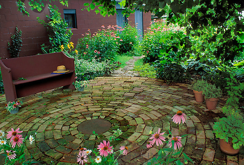 Circular shaded patio with wooden bench highlighted with pink coneflowers (echninacea) in pots