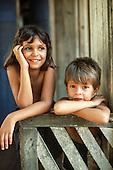 Xapuri, Acre State, Brazil. Smiling rubber tapper children - boy and girl -  outside their wooden house.