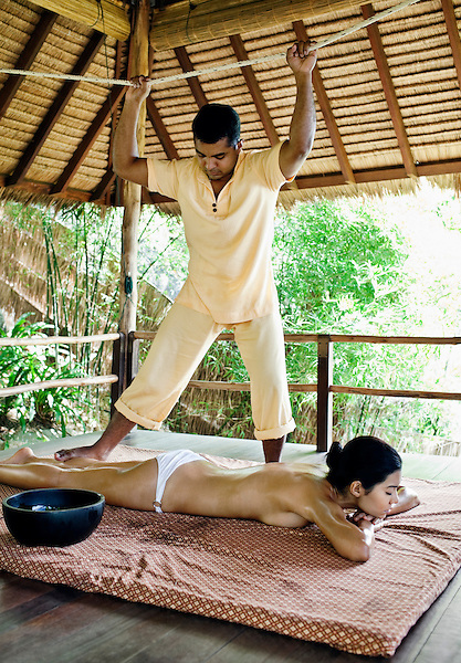 Woman Receiving Pathagajaily, Ayurvedic Massage at Kamalaya, Koh Samui, Thailand. A woman receives Pathagajaily Ayurvedic Massage at the spa at Kamalaya resort. Pathagajaily is an Indian Ayurvedic massage in which the therapist uses his or her feet to apply pressure to the body to alleviate muscle tension.
