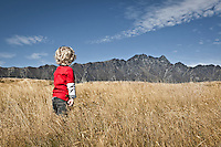 Young child looking towards the peaks of the Remarkables Mountains in Queenstown, South Island, New Zealand