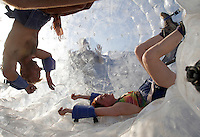 "BLACK ROCK CITY,NV - AUGUST 27,2008:  Experiences are a major theme of the  Burning Man Event,  interactive art, like this large infaltable rolling ball created by ""Dr. Dave""  encourage people to climb in and on the art. The week long event kicks into full gear as participants from around the world converge in Nevada for the annual art event. The event attracts over 30,000 people annually."