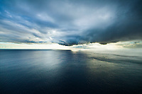 An aerial of storm clouds over the ocean as viewed from Kaua'i, with Ni'ihau in the distance.