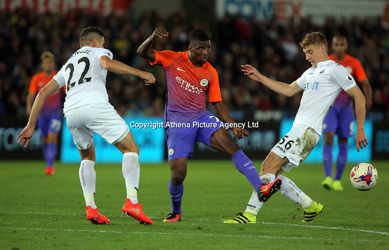 Kelechi Iheanacho of Manchester City (C) attempts to get past Angel Rangel (L) and Jay Fulton of Swansea City (R) during the EFL Cup Third Round match between Swansea City and Manchester City at The Liberty Stadium in Swansea, Wales, UK. Wednesday 21 September.